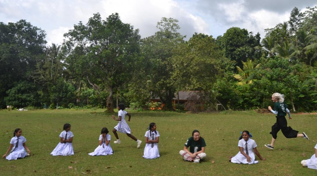 An instructor volunteers as a sports coach in schools in Sri Lanka and works with children